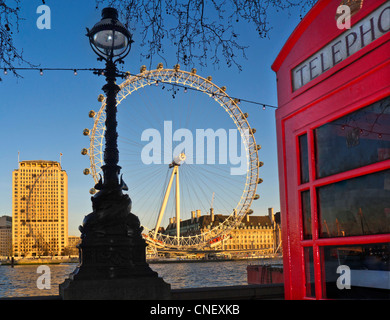 Traditional red telephone kiosk at Westminster Pier with River Thames and London Eye behind at sunset London UK - Stock Photo