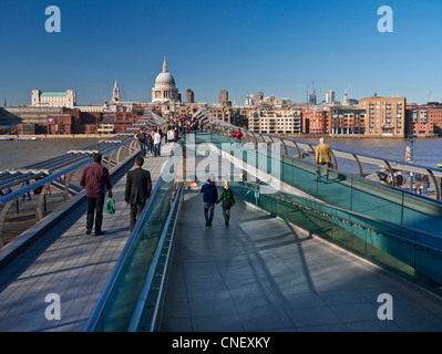 Millennium Bridge with visitors in crisp clear sunshine with St Paul's Cathedral at the focal point City of London - Stock Photo