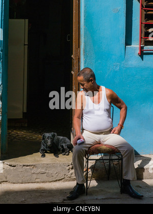 An older Cuban adult male sits on a chair outside the open door of his house and looks at his dog in Havana, Cuba. - Stock Photo
