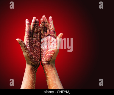 Beautiful henna or mehendi decoration on a hindu bride's hand with redish background with copy space. - Stock Photo