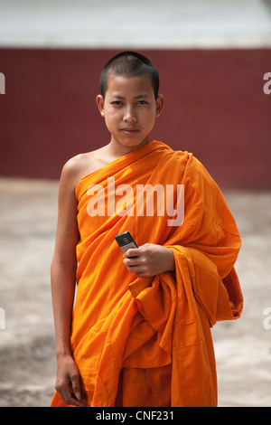 Young novice Buddhist Monk in saffron robes holding a mobile telephone. - Stock Photo