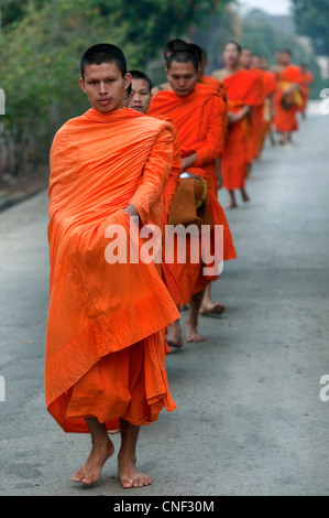 Barefooted Monks walking in procession wearing saffron robes during morning alms giving in Luang Prabang, Laos - Stock Photo