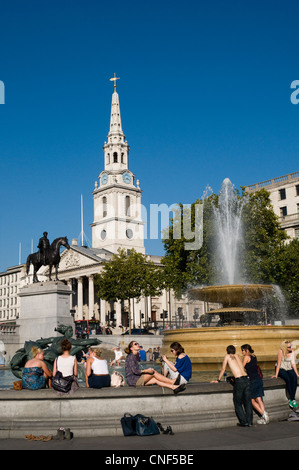 Tourist relax in the September sunshine while visiting Trafalgar Square. The statue of King George IV watches over - Stock Photo