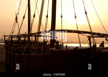 Silhouette of a Dhow at sunset in Kuwait with the city in the background. - Stock Photo