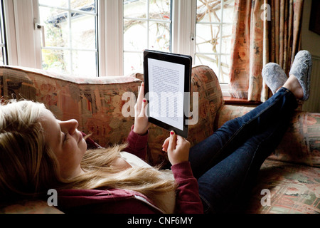 young teen woman reading an e-book on an iPad,  UK - Stock Photo