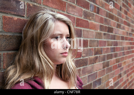 Blonde teenage girl leaning on a brick wall, head and shoulders portrait, Essex UK - Stock Photo