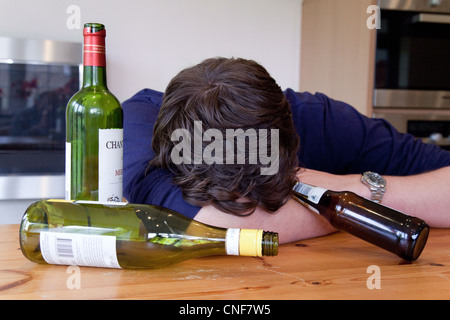 Drunk young man with hangover and empty bottles of wine and beer,  UK - Posed by a Model - Stock Photo