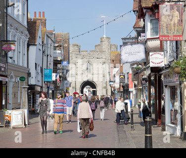 Canterbury UK High Street with Shoppers and Tourists enjoying a sunny day.  The famous Westgate Towers are in the background. Stock Photo