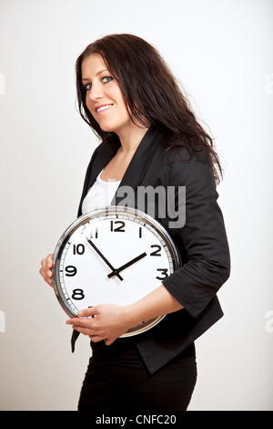 A portrait of a confident woman holding a clock with both hands - Stock Photo
