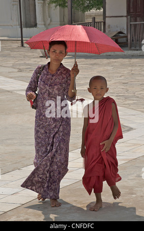 Mother and her novice monk son under a parasol. Kuthodaw Pagoda, Mandalay, Burma. Myanmar - Stock Photo