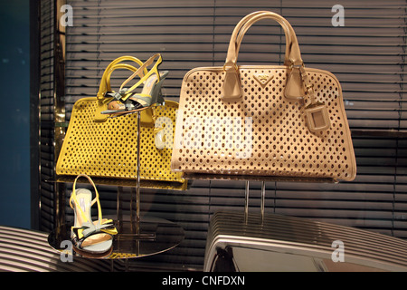 Luxury Prada handbags and high heel shoes in shop window in Marina Bay Sands, Singapore - Stock Photo
