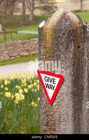 Modern give way sign on rural road fixed to old stone post - Stock Photo