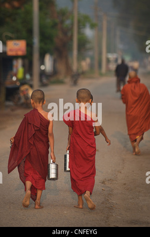 Novice buddhist Monks collecting alms at dawn, Hsipaw. Shan States, Burma. Myanmar - Stock Photo