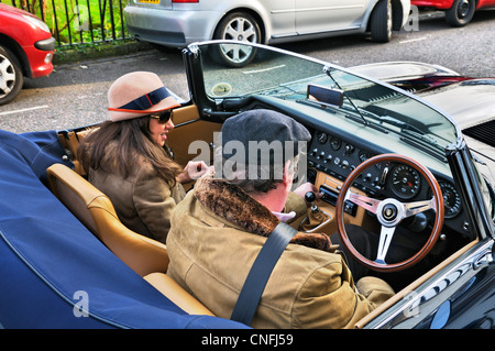 Lady and gent sitting in a E-type Jaguar classic car, London, England, UK - Stock Photo