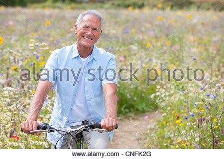 Smiling senior man riding bicycle on path through field of wildflowers - Stock Photo