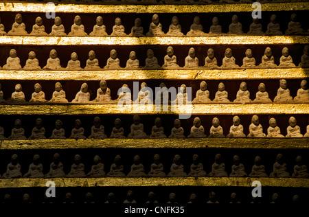 Dozens of small buddha images in sunlit niche, Thanboddhay Paya,  Monywa, Burma. Myanmar. Thambuddhei - Stock Photo