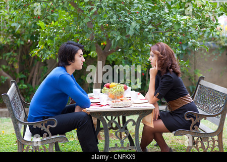 Two young people face off across a table at a restaurant during a disagreement in a sign of conflict - Stock Photo