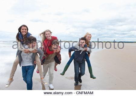 Enthusiastic teenage friends piggybacking on beach - Stock Photo