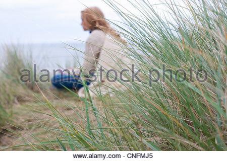 Teenage girl sitting in grass on beach - Stock Photo