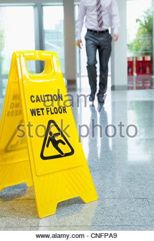 Businessman approaching wet floor sign on lobby floor - Stock Photo