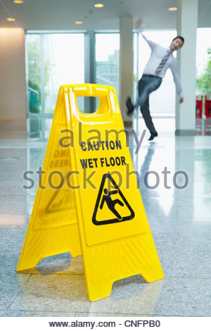 Businessman slipping behind wet floor sign in lobby - Stock Photo
