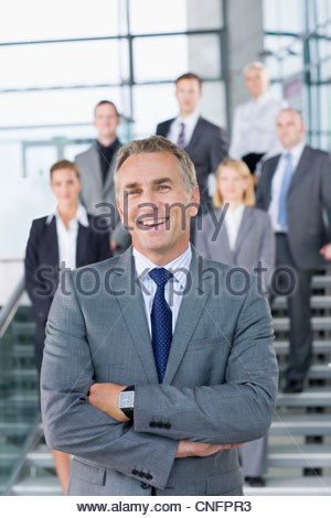 Portrait of smiling businessman in suit with business people in background - Stock Photo