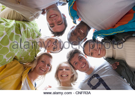 Low angle portrait of smiling friends in huddle - Stock Photo