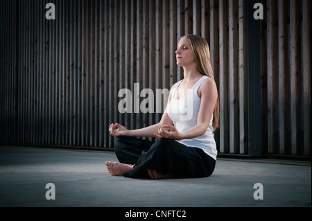 Young woman 20-25 sitting and meditating environment yoga meditation in a modern, cool, outdoor environment - Stock Photo