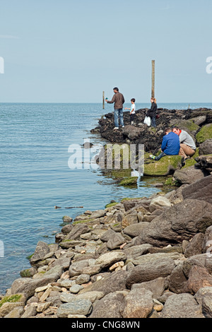 Family activity on a rocky beach at Lynmouth - Stock Photo