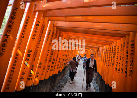 The tunnel and path of red torii gates leading to the Inner Shrine at Fushimi Inari Taisha shrine, in Inari, near - Stock Photo