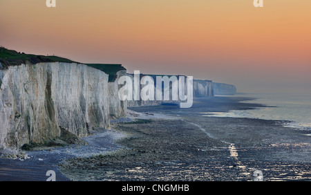 Eroded chalk cliffs and pebble beach along the English Channel at sunset near the village Ault, Picardy, France - Stock Photo
