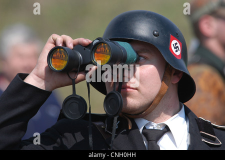 Nazi soldier looks through binocular produced in Russia. Re-enactment of the Battle for Orechov (1945) in Orechov - Stock Photo