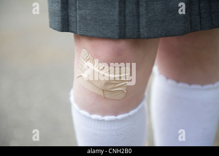 Schoolgirl's knee with a sticking plaster over a cut. - Stock Photo