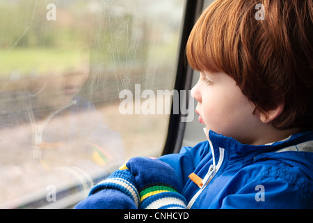 A young boy (three years old) looks out of the window whilst travelling on a train - Stock Photo