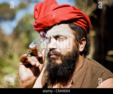 Baba smoking marijuana from clay pipe(chilum) Nepal - Stock Photo