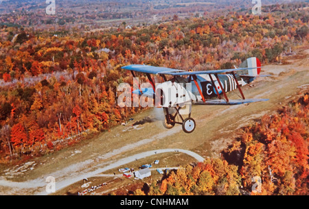 USA - CIRCA 1900 - This aged vintage postcard is a single engine airplane flying over autumn landscape, taken from - Stock Photo