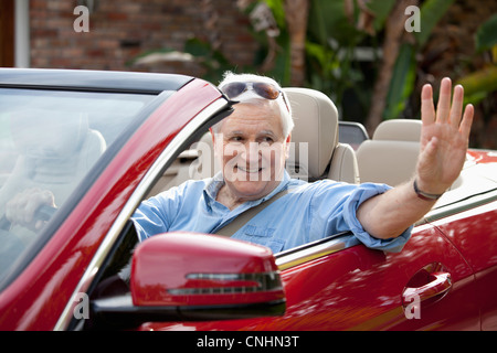 A senior man waving from driver's seat of convertible - Stock Photo