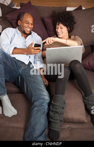 A couple reclining on a sofa sharing a laugh over something on a mobile phone - Stock Photo