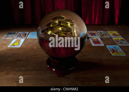A crystal ball with gold coins in the reflection and tarot cards in background - Stock Photo