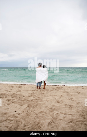 A young couple wrapped in a beach towel standing on the beach - Stock Photo