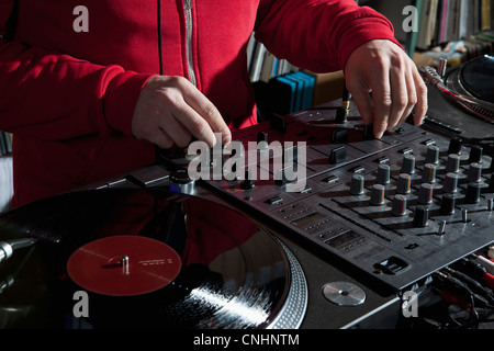 A DJ adjusting knobs on a sounder mixer, detail of hands - Stock Photo