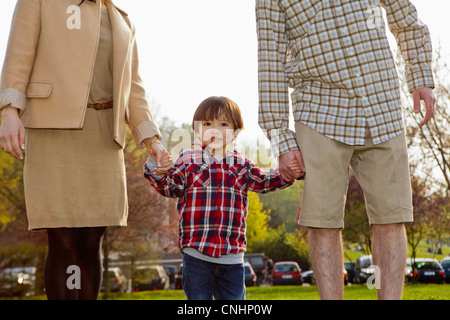 A young boy in between his parents, holding hands - Stock Photo