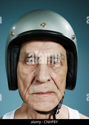 A headshot of a frowning senior man wearing a crash helmet - Stock Photo
