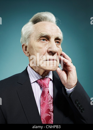 An elegant senior man looking away with a worried expression - Stock Photo