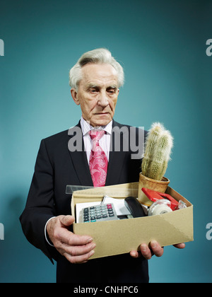 A senior man carrying a box of possessions after being fired - Stock Photo