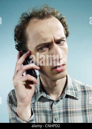 A man using a mobile phone and looking worried - Stock Photo