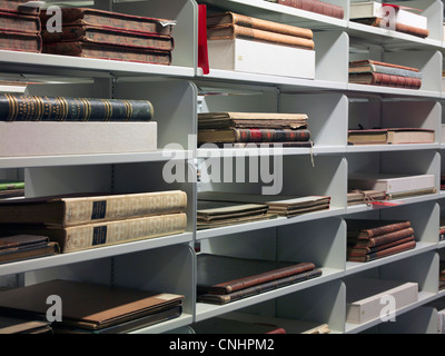 Detail of old books on shelves in a library - Stock Photo