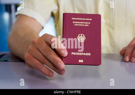 Detail of a man holding a German passport - Stock Photo
