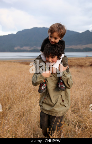 A teenage boy carrying his younger brother on his shoulders - Stock Photo