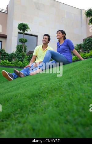Couple sitting on a lawn - Stock Photo